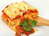 stock photo of lasagna  - Square of baked lasagna with parsley on bamboo serving spoon - JPG