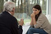 foto of psychologist  - Sad teenage girl talking with her psychologist - JPG