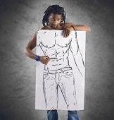 stock photo of physique  - Muscular man draws his perfect beautiful physique - JPG