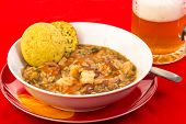 picture of creole  - Bowl of sausage and shrimp gumbo on bright red tablecloth with frothy mug of beer - JPG