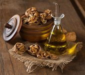 picture of walnut  - Walnut kernels whole and walnut oil on rustic old wooden table - JPG