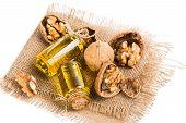 foto of walnut  - Walnut kernels whole and walnut oil on a burlap napkin isolated on white - JPG