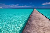 stock photo of jetties  - Wooden long jetty over lagoon in Maldives with amazing clean water - JPG