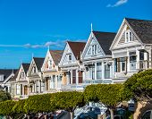 picture of victorian houses  - A capture of the famous Victorian Houses row in San Francisco taken from the city sidewalk on Steiner Street by Alamo Sqaure on the Sunny Day - JPG