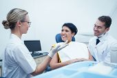 picture of dentist  - Male dentist and assistant with female patient in the dentists chair - JPG