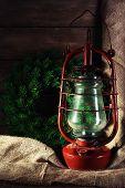 stock photo of kerosene lamp  - Kerosene lamp with wreath on wooden planks background - JPG