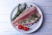 foto of pangasius  - Pangasius fillet with herb and sliced cherry tomatoes on plate and color wooden table background - JPG