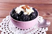 picture of doilies  - Dessert with prunes and almonds in bowl on lace doily and wooden planks background - JPG