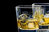 foto of shot glasses  - two glasses of alcoholic drink with ice on black background with space for text - JPG