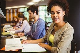 stock photo of thoughtfulness  - Student looking at camera while studying with classmates in library - JPG