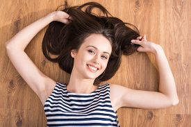 stock photo of stressless  - Top view of young woman is lying on the floor and looking at camera - JPG