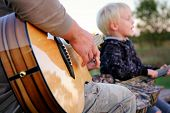 foto of singing  - Close up on exotic wood bottom of a guitar being played by a father as his sone sings in the background - JPG