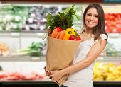 stock photo of grocery cart  - Smiling woman shopping in a supermarket - JPG