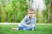 foto of sad boy  - portrait of a young sad boy with book on green grass - JPG