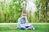 image of sad boy  - young sad boy with a books and laptop computer on green grass in the park - JPG