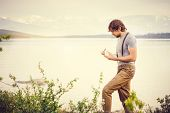 foto of scandinavian  - Young Man reading book and writing notes outdoor with scandinavian lake and mountains on background Education and Lifestyle Travel concept - JPG