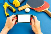 stock photo of ping pong  - Using smartphone with white screen on table with ping pong rackets - JPG