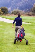 foto of caddy  - a golf player playing on a beautiful golf course and a golf bag full of golf clubs - JPG