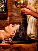 foto of massage oil  - Young woman having oil Ayurveda spa treatment - JPG