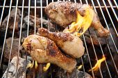 image of thighs  - Grilled chicken thigh over flames on a barbecue - JPG