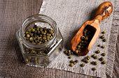 stock photo of peppercorns  - Green peppercorns in a glass jar on burlap - JPG