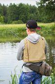 foto of fisherman  - Fisherman on the river bank in sunglasses - JPG