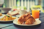 foto of orange-juice  - Croissant Breakfast served with black coffee and a breakfast menu such as orange juice jam eggs filling it - JPG