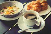 stock photo of breakfast  - Croissant Breakfast served with black coffee and a breakfast menu such as orange juice jam eggs filling it - JPG