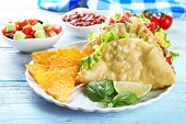 foto of tacos  - Tasty taco with nachos chips and vegetables on plate on table close up - JPG