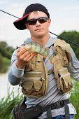 image of fisherman  - Young fisherman on the river bank - JPG