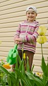 stock photo of red siding  - The girl of 9 years costs with a green watering can against a wall from a siding - JPG