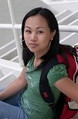 Asian Student With Backpack Sitting On Steps poster