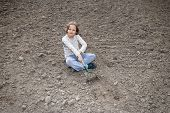 picture of hoe  - Girl digging in organic soil by hoe - JPG