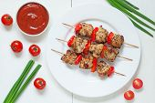 stock photo of kebab  - Traditional roasted turkey kebab skewer barbecue meat with vegetables and sauce on white dish - JPG