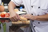 stock photo of chef knife  - Chef shred burger bun with knife  - JPG