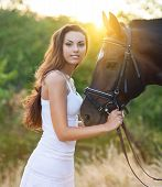 Image of beautiful happy woman with long hair next horse.