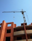 pic of construction crane  - Multistory building from brick under construction with no roof and construction crane - JPG