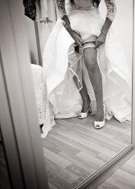 foto of garter-belt  - Bride on wedding day in white dress putting on garter belt shwing legs black and white photo - JPG