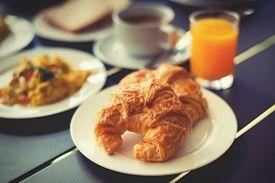 pic of breakfast  - Croissant Breakfast served with black coffee and a breakfast menu such as orange juice jam eggs filling it - JPG