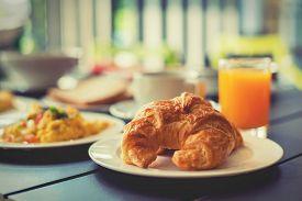 foto of breakfast  - Croissant Breakfast served with black coffee and a breakfast menu such as orange juice jam eggs filling it - JPG