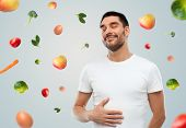Постер, плакат: food healthy eating diet and people concept happy full man touching his tummy over gray backgrou