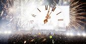 Colorful fireworks, clock close to midnight and crowd celebrating the New Year poster