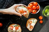 Woman holding delicious sandwich with cherry tomato and mozzarella over table, top view poster