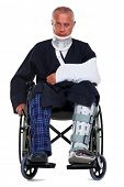 Photo of a mature male with various injuries in a wheelchair, he's wearing a neck brace, arm sling a