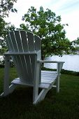 stock photo of nea  - a white beach chair nea rthe water ready for someone to sit and relax - JPG