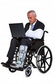 Photo of an injured businessman sitting in a wheelchair working on a laptop computer, isolated again