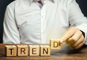 Businessman Puts Wooden Blocks With The Word Trend. Popular And Relevant Topics. New Ideological Tre poster