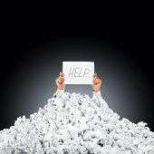 stock photo of piles  - Person under crumpled pile of papers with hand holding a help sign - JPG