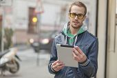 picture of serbia  - Young man with yellow glasses use iPad tablet computer on street - JPG