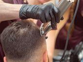 Females Hand In Black Rubber Glove Cutting Hair With Clipper, Close Up View. Stylist Making Modern H poster